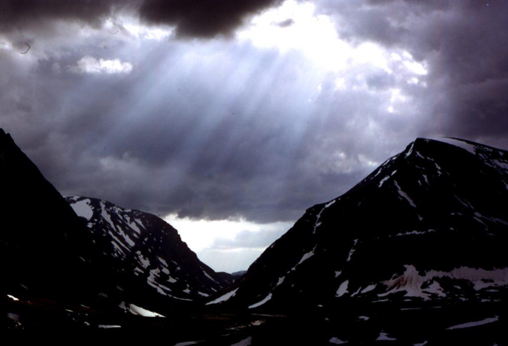 Fjäll med ljus som silar genom molnen