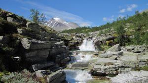 solig vy över vattenfall i fjällen