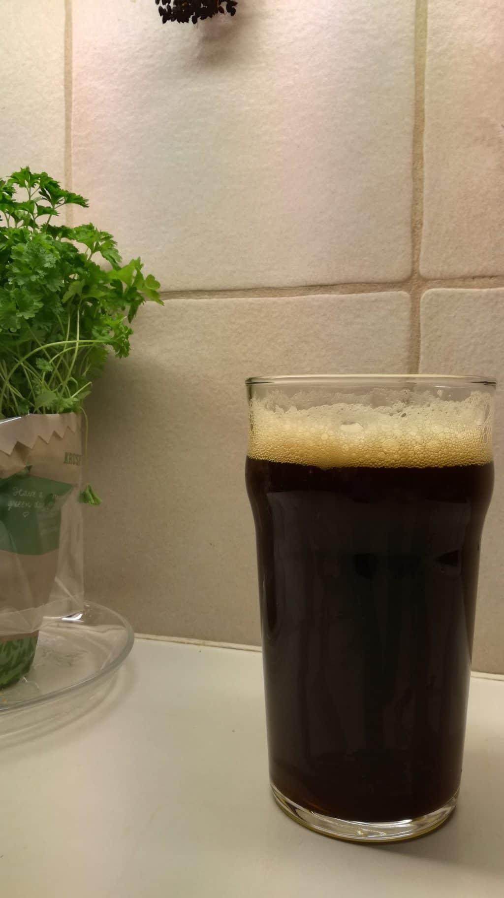 ett glas öl och en kruka persilja